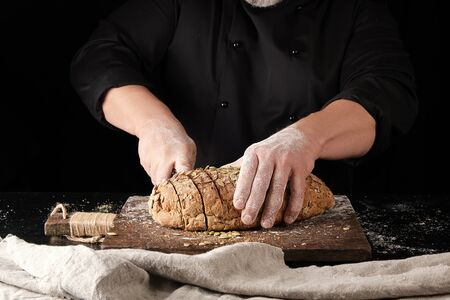 baker in black uniform cuts a knife into slices of rye bread with pumpkin seeds on a brown wooden board, black background