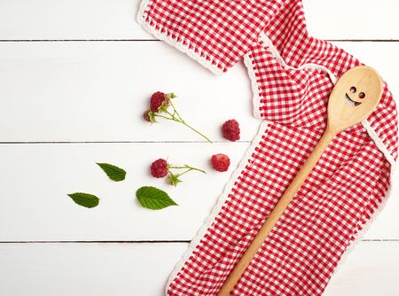 wooden spoon and textile red towel on a white wooden table, near raspberries, top view