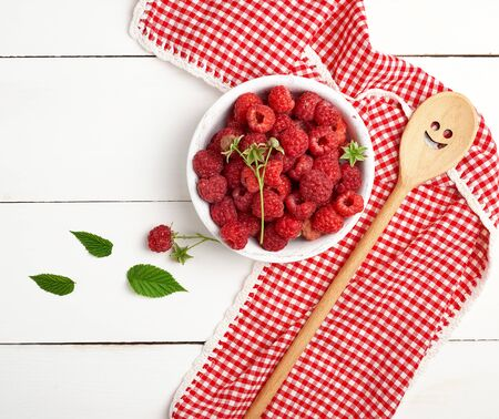 ripe red raspberries in a white wooden plate on a table of boards, next is a spoon and a textile towel, top view