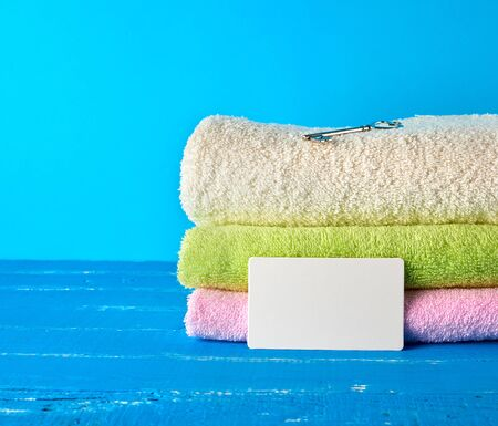 three multi-colored new terry bath towels folded on a blue wooden background and empty paper business cards