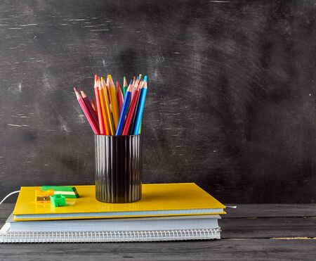 stack of notebooks, black stationery glass with multi-colored wooden pencils on the background of an empty black chalk board, back to school concept