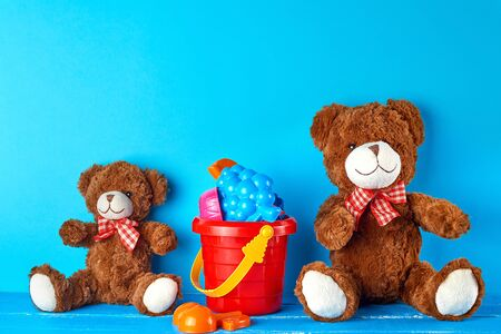 two brown teddy bears on a blue background, friendship concept, copy space