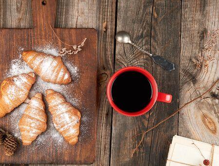 keramische rode kop met zwarte koffie en houten snijplank met gebakken croissants, gebakken met poedersuiker, bovenaanzicht Stockfoto