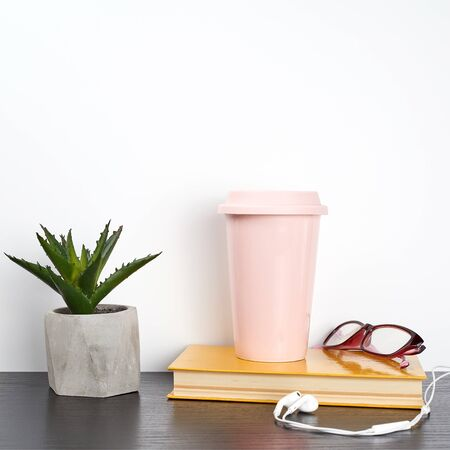 closed book and pink ceramic glass with coffee on a black table, white wall Stockfoto