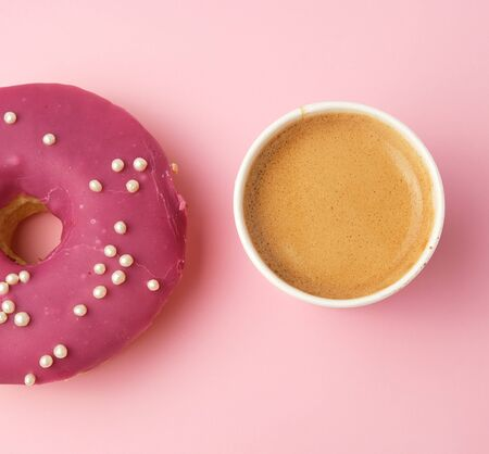 round red glazed donut and paper cup with coffee on a pink background, top view