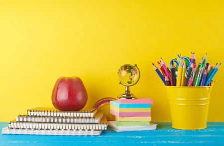 background back to school with children's stationery pencils, notepad, apple, glass globe on a yellow  background