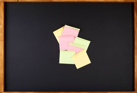 empty square multi-colored stickers hang on a black board in a wooden frame, business concept