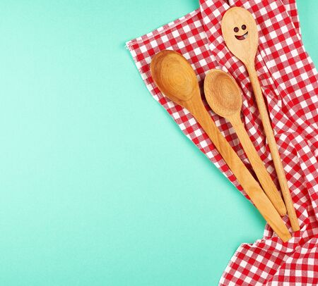 wooden spoon with a carved face on a red kitchen towel, green background, copy space