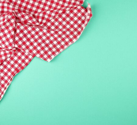 white red checkered kitchen towel on a green background, bright picnic background, copy space