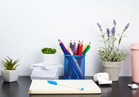 spiral notebooks, ceramic cup with coffee and colorful pencils on a black table, work space