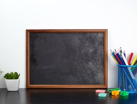 empty black chalk board, multi-colored pencils in a blue metal stand on a black table, concept back to school