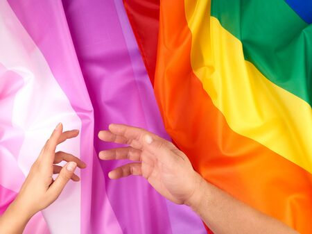 female and male hand outstretched against the background of flags of LGBT communities, concept against gender discrimination Reklamní fotografie