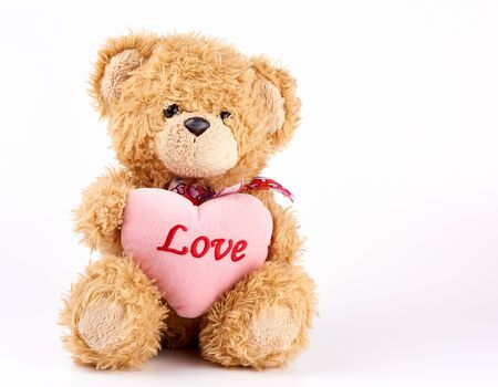 beige teddy bear holds a pink heart, white background, copy space