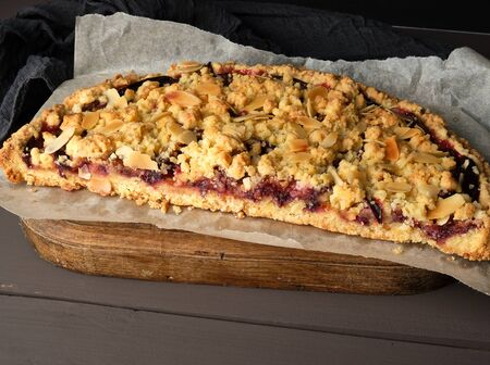 half plum pie crumble on a brown wooden cutting board, close up Stock Photo