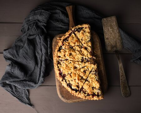 half plum pie crumble on a brown wooden cutting board, top view