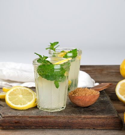 summer refreshing drink lemonade with lemons, mint leaves in a glass, next to the ingredients for making a cocktail Standard-Bild - 129453423