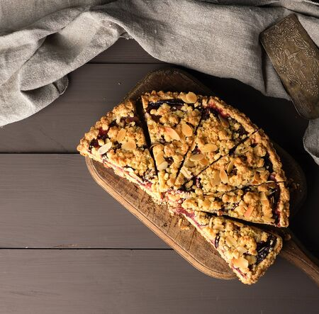half plum pie crumble on a brown wooden cutting board, top view Stock Photo - 129555369