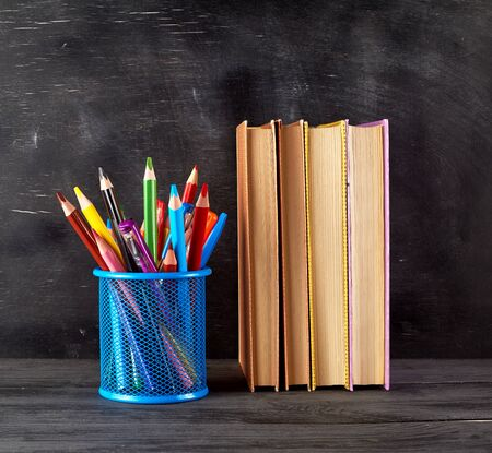stack of books and a blue stationery glass with multi-colored wooden pencils, background of an empty black chalk board, back to school concept Stock Photo