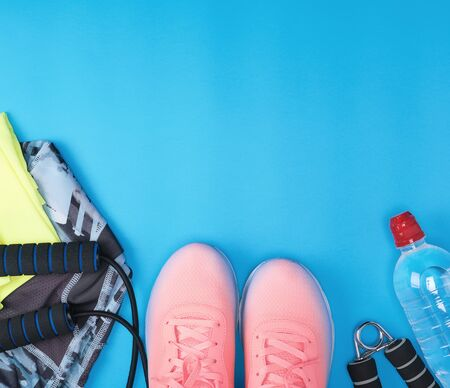sport textile shoes and other items for fitness on a blue background, top view, copy space