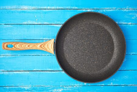 new empty frying pan with a brown handle on a blue wooden background, bottom with a crumb of stone and marble