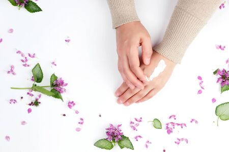 two female hands and a thick cream, top view, concept of anti-aging procedures for rejuvenating and moisturizing the skin of hands