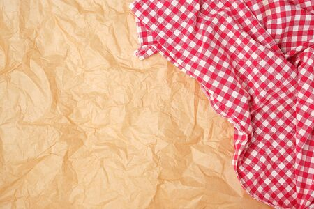 white red checkered kitchen towel on a brown paper background, bright picnic background, copy space