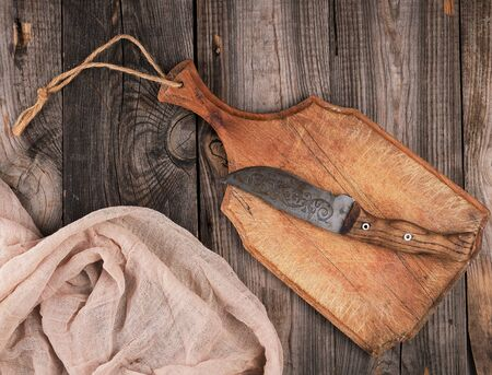 empty old brown wooden cutting board with handle and gray textile napkin, top view