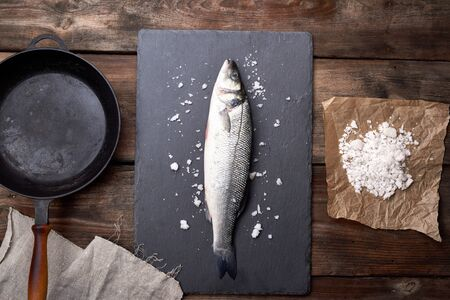 fresh whole sea bass fish on a black board, next to it is an empty round black frying pan on a wooden table, top view Stock Photo
