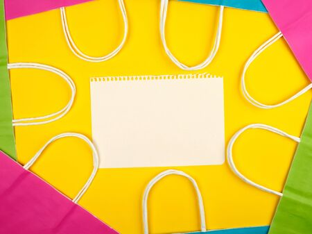 blank white sheets and multi-colored paper shopping bags with white handles on a yellow background, flat lay