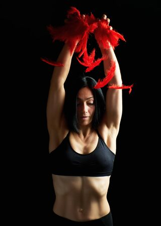 young beautiful athletic girl in black clothes throws up red feathers, arms raised up, low key Фото со стока