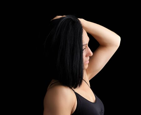Adult girl with a sports figure in black bra standing on a dark background, model is turned sideways and straightens her black hair, low key Фото со стока