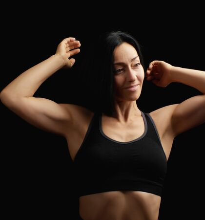Adult girl with a sports figure in black bra standing on a dark background, muscular body, black hair