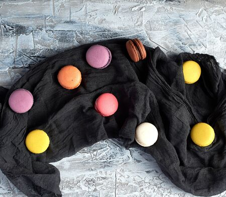 round multi-colored baked macaroons with cream on a black gauze towel, top view