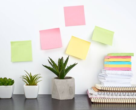 stack of spiral notebooks and colored stickers, next to a ceramic pot with a flower on a black table, white wall, Scandinavian-style minimalism