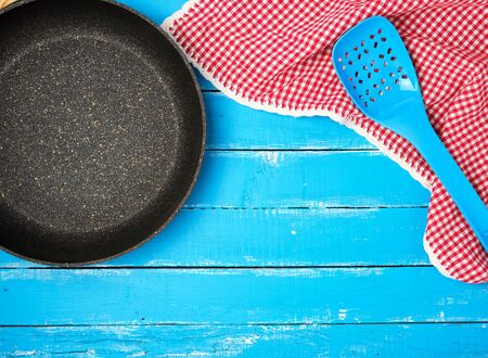 empty black round nonstick frying pan with handle on blue wooden background with red napkin, top view