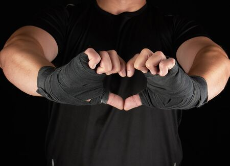 athlete shows the symbol of the heart, palm of a man is wrapped in a black sports bandage, black background Stock fotó