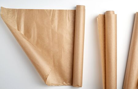 rolled rolls of parchment baking paper on a white background, top view