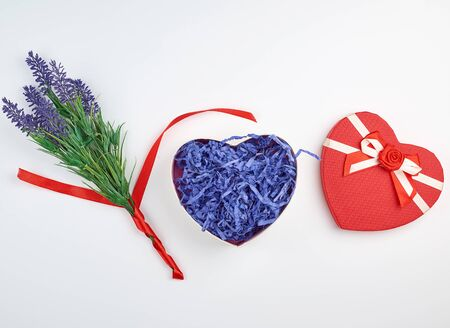 open red heart-shaped gift box with a bow on a white background, top view, festive backdrop Stock Photo
