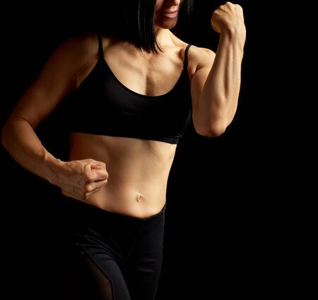 Adult girl with a sports figure in black bra and black shorts standing on a dark background, muscular body, black hair