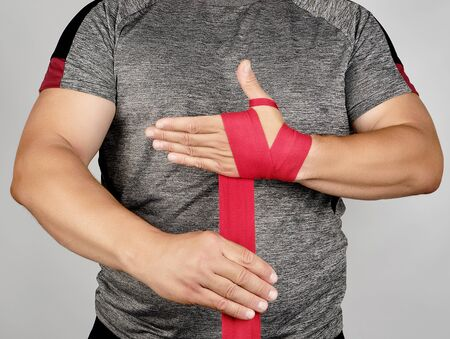 athlete stand in gray clothes and wrap his hands in red textile elastic bandage before training, gray background Banque d'images - 130735927