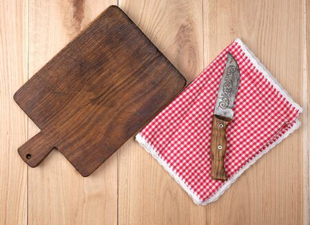 empty old wooden kitchen cutting board and knife on a table, top view