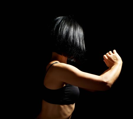 body of a girl of athletic appearance in a black bra, athlete stands sideways, low key