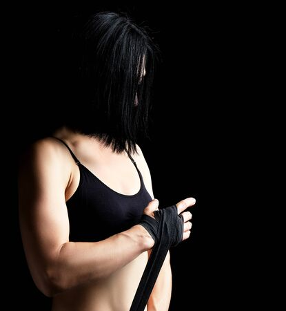beautiful athletic girl with black hair rewinds her hand with a black elastic bandage before training,  dark background