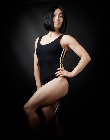 young woman in a black bodysuit posing on a dark background, black hair and a muscular sports figure