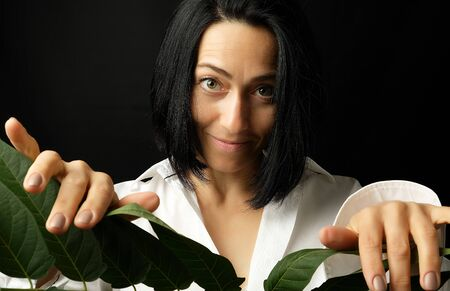 portrait of a beautiful adult woman with short black hair of a Caucasian appearance dressed in a white shirt holds a branch with green leaves, black background