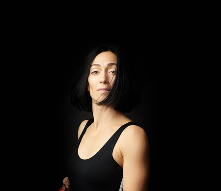 portrait of a beautiful young woman with black hair on a dark background, emotional impulse
