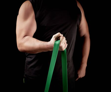 athlete with a muscular body in black clothes is doing physical exercises with green rubber, low key Stock Photo