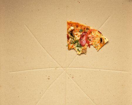Pizza mordida con salchichas ahumadas, champiñones, queso y tomates en una caja de cartón marrón, vista superior