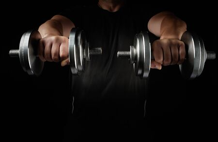 two steel typesetting dumbbells in male hands, arms extended forward and muscles tense, sports backdrop, low key