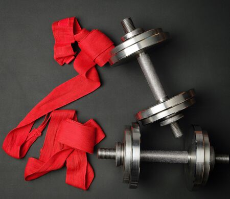 pair of shiny steel typesetting dumbbells for bodybuilding and textile bandage on a black background, top view